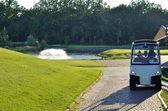 Golf cart over nice green grass and blue sky — Stok fotoğraf