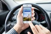 IPhone 5S app TripAdvisor in hands of the driver car — Stock Photo