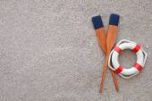 Paddles and life buoy lying on a sand — Stock Photo