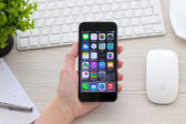 Woman holding iPhone 6 Space Gray over the table — Стоковое фото