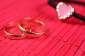 Orange gold-plated heart with two wedding rings — Stock Photo