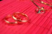 Two gold wedding rings and gold heart — Stock Photo