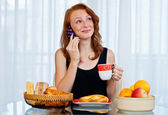 Attractive girl with freckles eating breakfast — Stock Photo