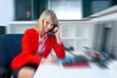 Attractive blond woman in office talking to phone — Stock Photo