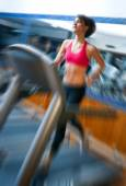 Woman in gym running on track — Stock Photo