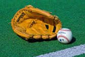 Baseball glove and ball on the field — Stock Photo