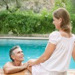 Couple relaxing together on the egde of a swimming pool — Stock Photo #78500814