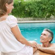 Couple relaxing together on the egde of a swimming pool — Stock Photo #78501344