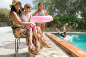 Family in a holiday home garden with a swimming pool — Stock Photo