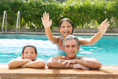 Family relaxing in swimming pool — Stock Photo