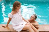 Couple relaxing together on the egde of a swimming pool — Stock Photo