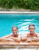 Couple relaxing in a swimming pool — Stock Photo