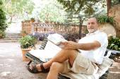Man sitting on a bench and reading a newspaper — Stock Photo