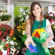 Woman with a bouquet of fresh flowers and credit card — Stock Photo #79000728