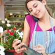 Florist woman using the phone with a clipbard in her store — Stock Photo #79003120