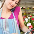 Florist woman using the phone with a clipbard in her store — Stock Photo #79003122