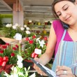 Florist woman using the phone with a clipbard in her store — Stock Photo #79003138