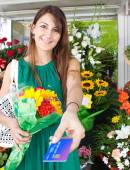 Woman with a bouquet of fresh flowers and credit card — Stock Photo