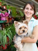 Florist woman holding a dog in her store — Stock Photo