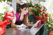 Florist woman using a laptop in her store — Stock Photo