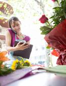 Florist woman using the phone with a clipbard in her store — Stock Photo