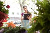 Florist woman with a clipbard in her store — Stock Photo