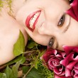 Woman laying in a forest wearing a red roses head dress — Stok fotoğraf #79453436