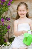 Girl holding a small watering can — Stock Photo