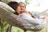 Daughter and her mother laying together in a hammock — Stockfoto