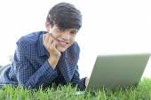 Boy using a laptop computer on the grass — Stock Photo