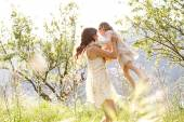 Mother and daughter hugging in a spring field — Stock Photo