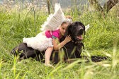Girl sitting on her dogs in a park field — Stock Photo