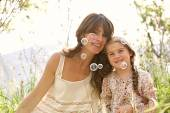 Mother and daughter playing to blow floating bubbles — Stock Photo