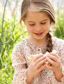 Girl eating a fresh sandwich in a field — Stock Photo