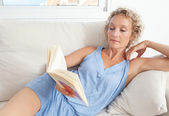 Woman reading book on a sofa at home — Stock Photo