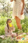 Mother and daughter having a picnic in a garden — Stock Photo