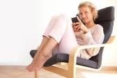 Woman in an armchair using a smartphone — Stock Photo