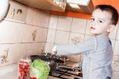 Wounded in the left hand with bandage boy at shot in home kitche — Stockfoto
