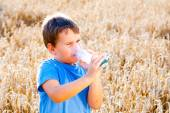 Boy using inhaler for asthma in village with summer sunset — Stock Photo