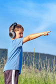Cute 6 year old boy listening to music on headphones in nature — Stock Photo
