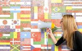 Pretty girl shouting with a megaphone over flags background  — ストック写真