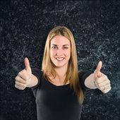 Blonde girl making Ok sign over black background — ストック写真