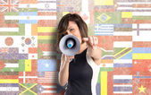Pretty girl shouting with a megaphone over flags background  — Stock Photo
