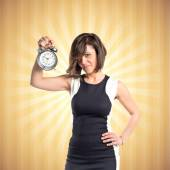 Pretty woman holding an antique clock over pop background  — Stock Photo