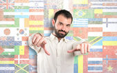 Young man pointing opposite over flags background — Stock Photo