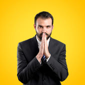 Young businessman pleading over yellow background  — Stock Photo