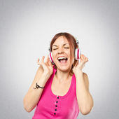 Young girl listening music over grey background — Stock Photo