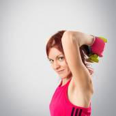 Redhead girl doing weightlifting over grey background,  — Stock Photo