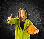 Young girl with thumb up over black background — Stock Photo