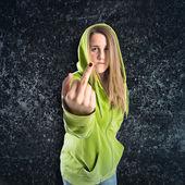 Girl making horn gesture over black background — ストック写真